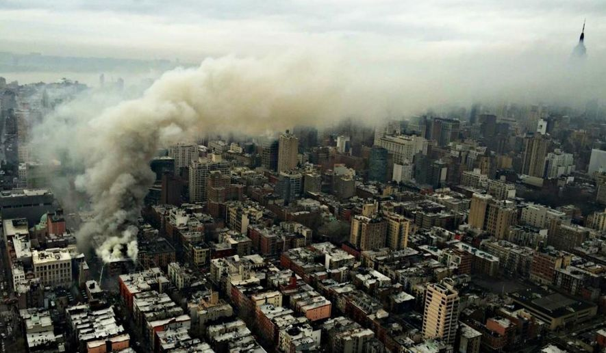In this photo provided by the NYPD Special Ops, smoke rises from the scene of a large fire and a partial building collapse in the East Village neighborhood of New York on Thursday, March 26, 2015. Orange flames and black smoke are billowing from the facade and roof of the building near several New York University buildings. (AP Photo/NYPD Special Ops)
