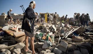 A Houthi Shiite fighter stands guard as people search for survivors under the rubble of houses destroyed by Saudi airstrikes near Sanaa airport in Yemen, Thursday. Saudi Arabia launched airstrikes targeting military installations in Yemen held by Shiite rebels. (Associated Press)