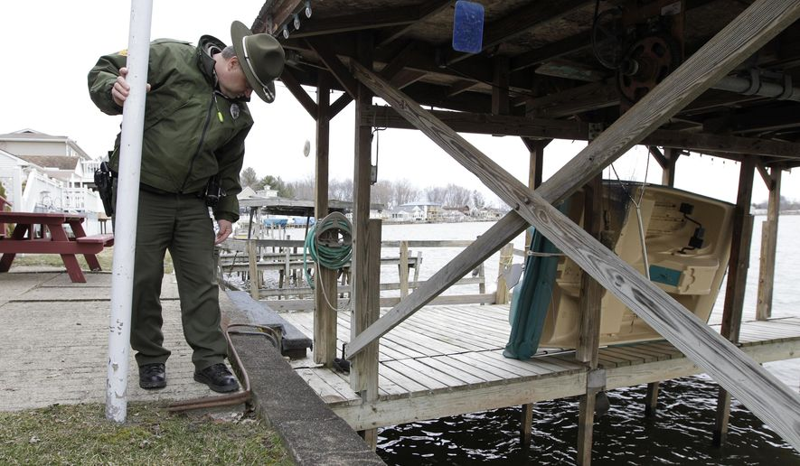 Buckeye Lake State Park manager Jason Wesley inspects part of the dam at Buckeye Lake Monday, March 23, 2015, in Buckeye Lake, Ohio.   The earthen dam at central Ohio's Buckeye Lake is deteriorating, which perhaps isn't surprising for a 180-year-old structure. Since the state sold parts of it for private use in 1895, bits and chunks have been carved away.   When a report this month warned the dam could fail, the state decided to replace it and keep the water level low for now.  Businesses and residents worry about the effect on tourism, property values and local lifestyles. (AP Photo/Jay LaPrete)