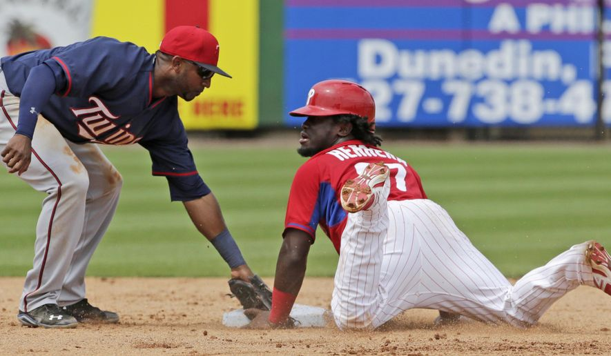Minnesota Twins shortstop Eduardo Nunez , left, puts the tag on Philadelphia Phillies Odubel Herrera, but Herrrera  is safe on a fifth-inning stolen base in a spring training baseball game in Clearwater, Fla., Monday, March 23, 2015. (AP Photo/Kathy Willens)