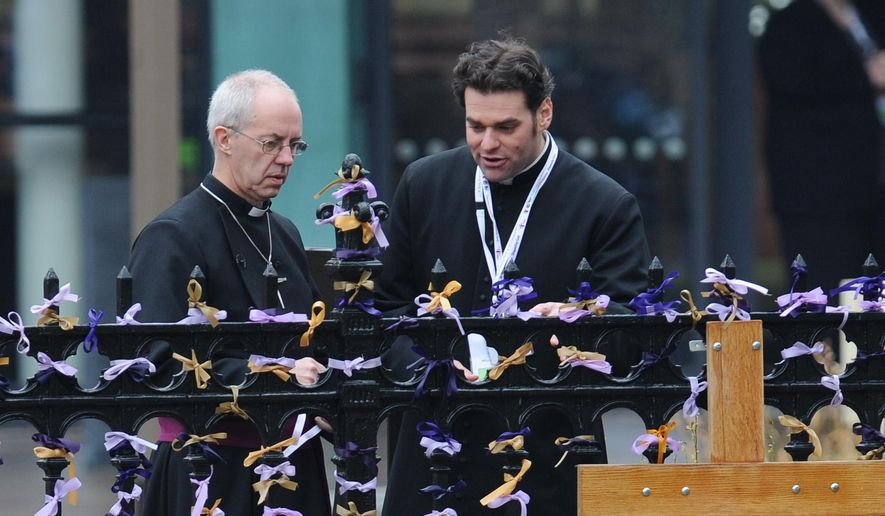 The Archbishop of Canterbury, Justin Welby, left, looks at pray ribbons outside Leicester Cathedral to attend a service for the re-reinterment of the mortal remains of Richard III at Leicester Cathedral, Leicester, England, Thursday, March 26, 2015. The skeleton of King Richard III was discovered in 2012 in the foundations of Greyfriars Church, Leicester, 500 years after he was killed in the Battle of Bosworth Field. (AP Photo/Rui Vieira)