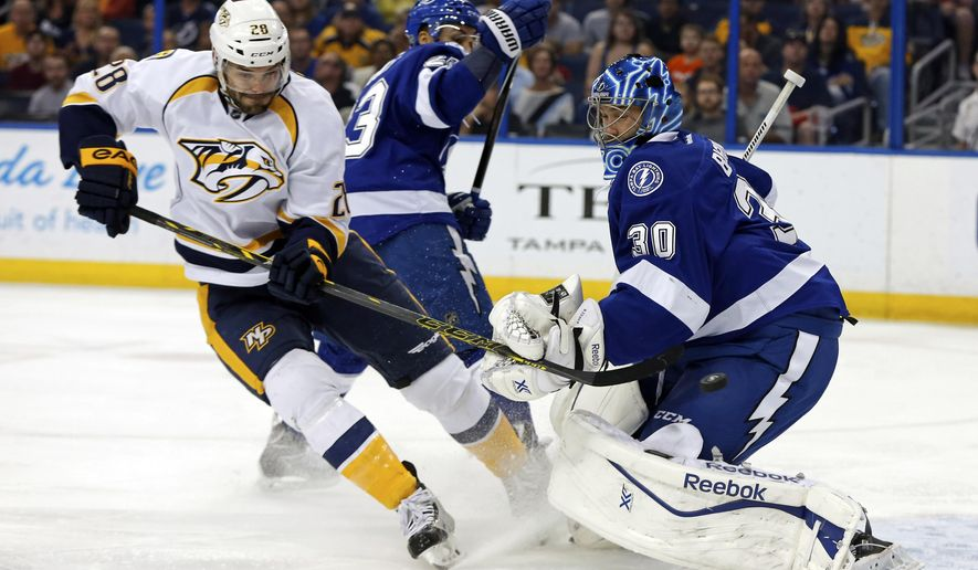 Nashville Predators' Paul Gaustad, left, tips a puck past Tampa Bay Lightning goalie Ben Bishop to score during the first period of an NHL hockey game Thursday, March 26, 2015, in Tampa, Fla. (AP Photo/Mike Carlson)