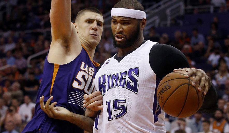 Sacramento Kings center DeMarcus Cousins (15) drives on Phoenix Suns center Alex Len during the first quarter of an NBA basketball game, Wednesday, March 25, 2015, in Phoenix. (AP Photo/Rick Scuteri)