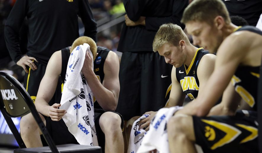 FILE - In this March 22, 2015, file photo, Iowa's Aaron White, left, and teammates rest during a timeout against Gonzaga in the second half of an NCAA tournament college basketball game in the Round of 32 in Seattle. In the NCAA tournament, more frequent stoppages in play-- leave coaches and players with time on their hands. (AP Photo/Elaine Thompson, File)