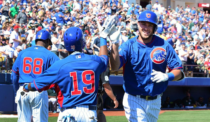 FILE - In this March 14, 2015, photo provided by the Las Vegas News Bureau, Chicago Cubs' Kris Bryant, right, celebrates with a teammate after hitting a home run in the third inning of a spring training baseball game against the Oakland Athletics in Las Vegas. The last crown they wore came in 1908, before Wrigley Field was built. Now, as the old ballpark gets renovated, the franchise is being refurbished, too. (AP Photo/Las Vegas News Bureau, Steve Spatafore, File)