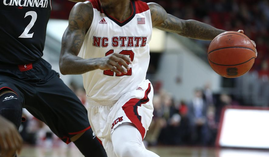 """FILE - North Carolina State's Cat Barber (12) drives around Cincinnati's Octavius Ellis (2) during the first half of NCAA college basketball game in this Dec. 30, 2014 file photo taken in Raleigh, N.C. Barber used an unexpected Sweet 16 berth to take a cutting remark at President Barack Obama. He was caught by TV cameras Saturday March 21, 2015 saying """"What ... (is) wrong with Barack Obama"""" to his teammates in the locker room.  (AP Photo/The News & Observer, Ethan Hyman, FILE)"""