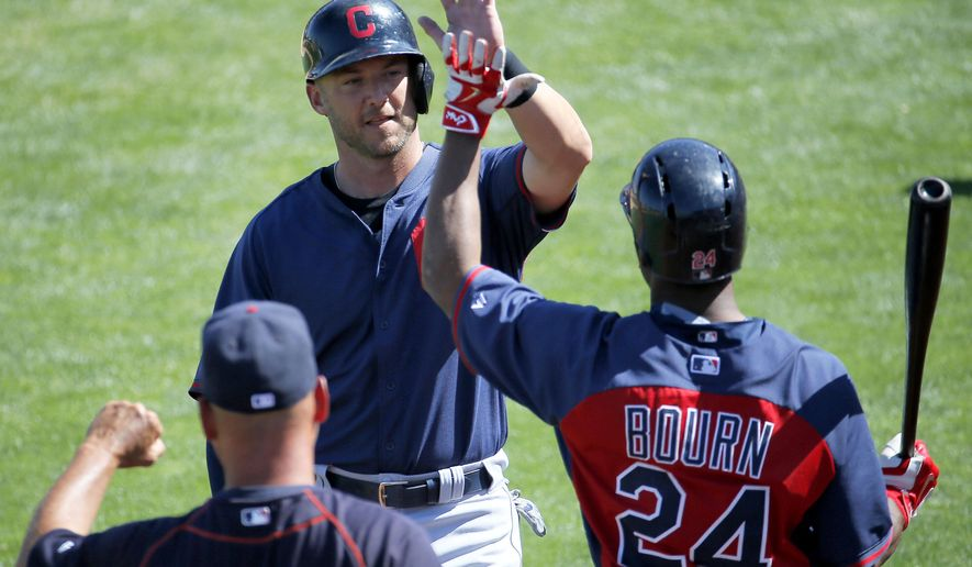 Cleveland Indians' Ryan Raburn high fives Michael Bourn (24) after scoring on an RBI double by teammate Destin Hood against the Los Angeles Angels during the fourth inning of a spring training baseball game, Wednesday, March 25, 2015, Tempe, Ariz.  (AP Photo/Matt York)