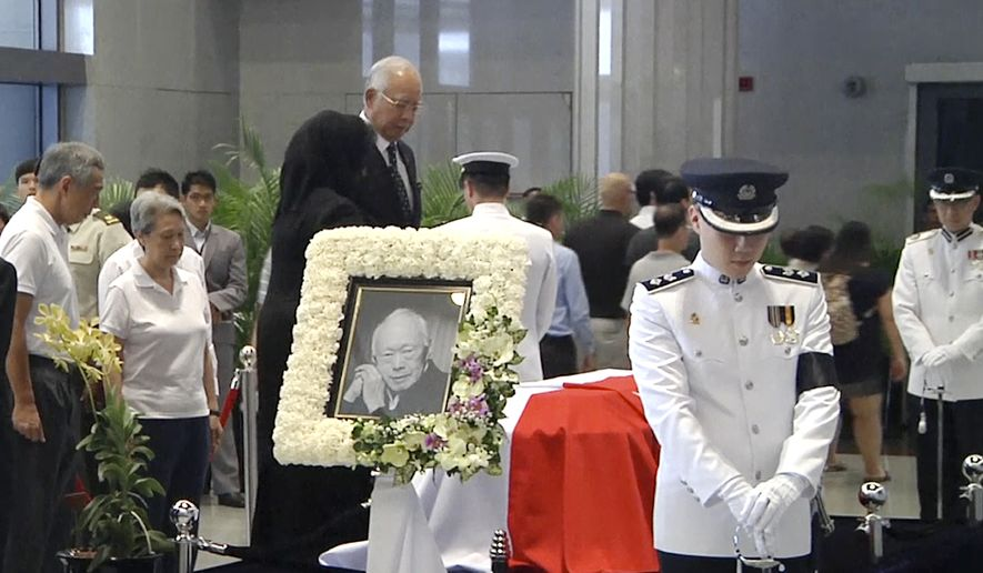 In this image made from APTN video, Malaysia's Prime Minister Najib Razak, center, and his wife Rosmah Mansor pay respects to the late Lee Kuan Yew, as Singapore Prime Minister Lee Hsien Loong, left, and his wife Ho Ching, second left, stand at left, the Parliament House where he will lie in state for four days, Thursday, March 26, 2015, in Singapore. Lee, 91, died Monday after more than a month of battling severe pneumonia. (AP Photo/APTN)