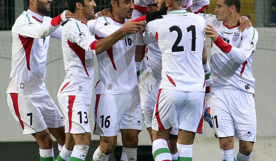 Iran players celebrate scoring against Chile during the friendly soccer match between Iran and Chile in St. Poelten, Austria, Thursday, March 26, 2015. (AP Photo/Ronald Zak)