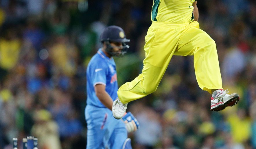 Australia's Mitchell Johnson leaps in the air as he celebrates after taking the wicket of India's Rohit Sharma, left, during their Cricket World Cup semifinal in Sydney, Australia, Thursday, March 26, 2015. (AP Photo/Rob Griffith)