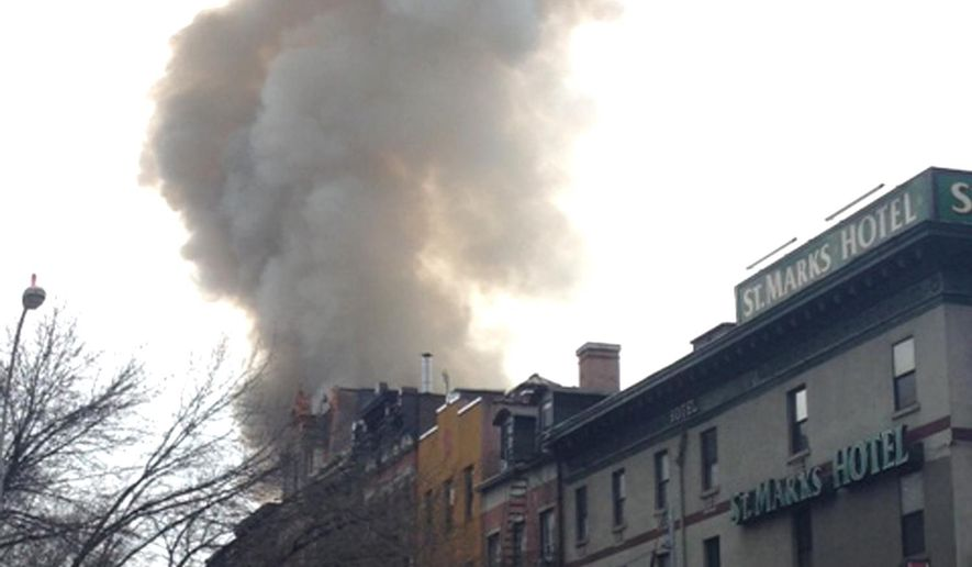 Smoke billows from a building in New York's East Village neighborhood at the scene of a large fire and a partial building collapse. There were some reports of an explosion before the fire and the area was being evacuated. (AP Photo/Jonathan Lemire)