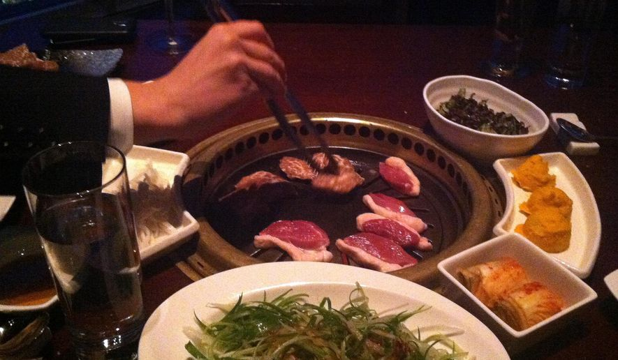 This Feb. 26, 2015 photo shows meat being cooked on a tableside Korean barbecue grill at Gaonnuri restaurant in New York. Gaonnuri is located on the 39th floor in the penthouse of a building on West 32nd Street, known as Korea Way. The district, also called Koreatown or K-town, is known for Korean restaurants and karaoke bars. (AP Photo/Beth J. Harpaz)