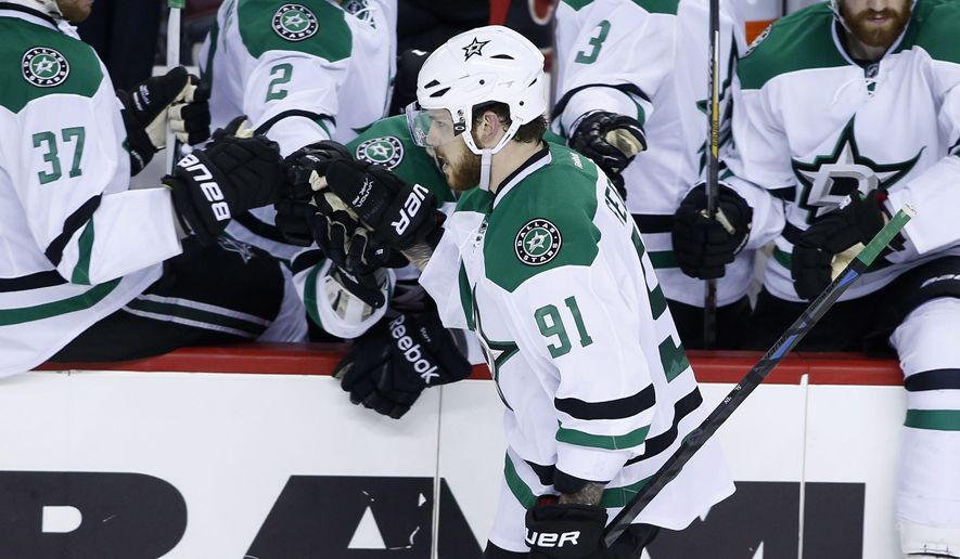 Dallas Stars' Tyler Seguin, center, celebrates his shootout goal against the Calgary Flames during an NHL hockey game Wednesday, March 25, 2015, in Calgary, Alberta. Dallas won 4-3. (AP Photo/The Canadian Press, Larry MacDougal)