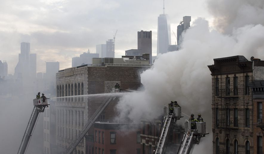 New York City firefighters on ladders spray water at the scene of a fire and a partial building collapse in the East Village neighborhood of New York on Thursday, March 26, 2015. (AP Photo/John Minchillo)