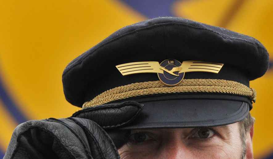 FILE - In this Feb. 22, 2010 file picture, a Lufthansa Airlines pilot holds the brim of his cap at the airport in Frankfurt, Germany. Carsten Spohr, CEO Lufthansa _ the parent company of Germanwings _ says his pilots undergo yearly medical examination but that doesn't include psychological tests. (AP Photo/dpa, Boris Roessler, File)