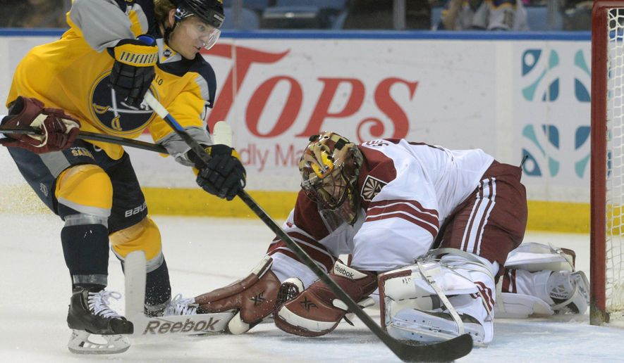 Buffalo Sabres center Tyler Ennis, left, skates around Arizona Coyotes goaltender Mike Smith for a goal during the first period of an NHL hockey game Thursday, March 26, 2015, in Buffalo, N.Y. (AP Photo/Gary Wiepert)