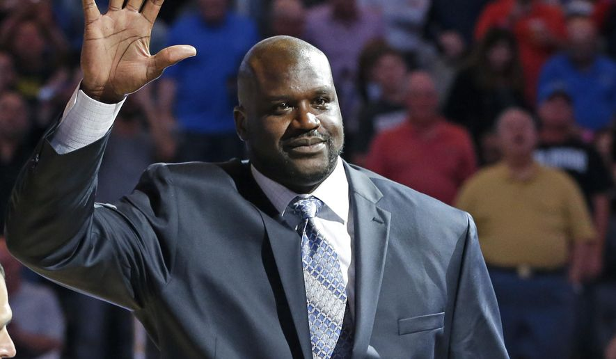 Former NBA basketball player Shaquille O'Neal waves to fans as he is honored during an NBA basketball game between the Orlando Magic and the Detroit Pistons after he was inducted in the Magic Hall of Fame, Friday, March 27, 2015, in Orlando, Fla. Selected by Orlando with the first overall pick of the 1992 NBA Draft, O'Neal spent four seasons with the Magic from 1992-96. (AP Photo/John Raoux)