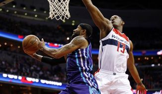 Charlotte Hornets guard Mo Williams (7) shoots past Washington Wizards center Kevin Seraphin (13), from France, in the first half of an NBA basketball game Friday, March 27, 2015, in Washington. (AP Photo/Alex Brandon)