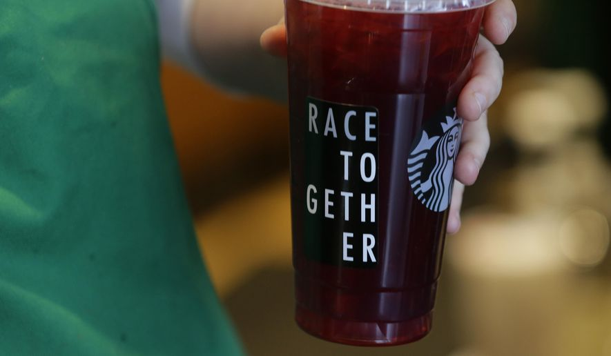 """In this March 18, 2015 photo, a Starbucks barista holds an iced tea drink with a """"Race Together"""" sticker on it at a Starbucks store in Seattle. Starbucks' effort to spark a dialogue on race caused an outcry from customers on social media and elsewhere. (AP Photo/Ted S. Warren)"""
