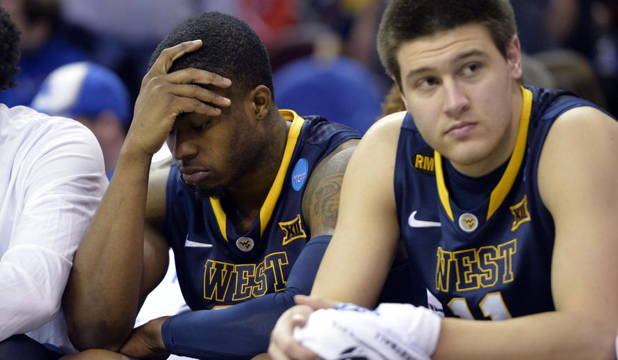 West Virginia's BillyDee Williams, left, and Nathan Adrian watch form the bench during the second half of the team's college basketball game against Kentucky in the NCAA men's tournament regional semifinals, Thursday, March 26, 2015, in Cleveland. (AP Photo/David Richard)