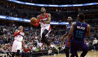 Washington Wizards guard John Wall (2) drives to the basket past Charlotte Hornets center Al Jefferson (25) and guard Kemba Walker (15) in the second overtime of an NBA basketball game Friday, March 27, 2015, in Washington. The Wizards won 110-107. (AP Photo/Alex Brandon)