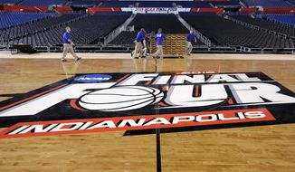 Workers at Lucas Oil Stadium install the court in Indianapolis, Friday, March 27, 2015,  as they prepare to host the NCAA Final Four college basketball games on April 4 and 6. (AP Photo/Michael Conroy)