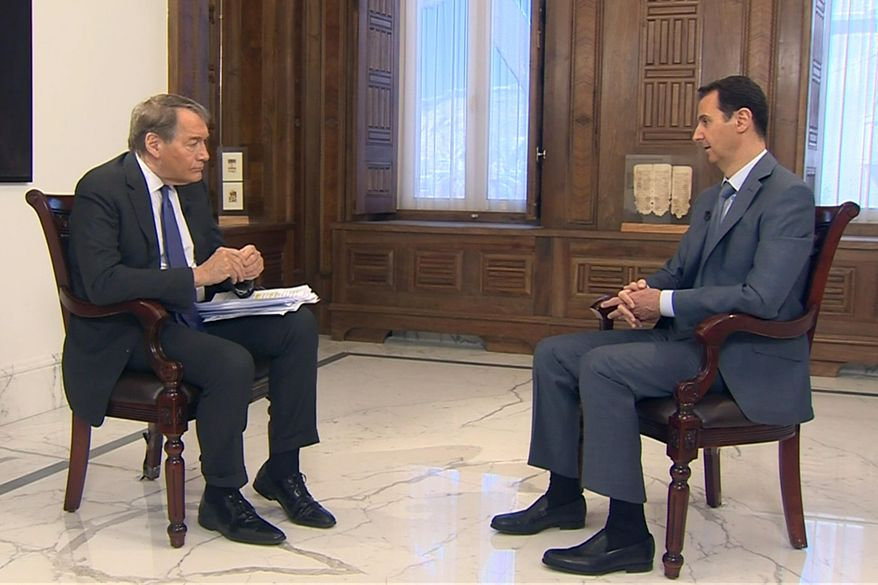 """In this frame grab from video provided by CBSNews/60 Minutes, in New York, """"60 Minutes"""" contributor Charlie Rose, left, interviews Syrian President Bashar Assad, Thursday, March 26, 2015, in Damascus, Syria. Assad says he would be open to a dialogue with the United States, but that it must be """"based on mutual respect,"""" during the interview scheduled to be broadcast Sunday, March 29. (AP Photo/CBSNews/60 Minutes)"""