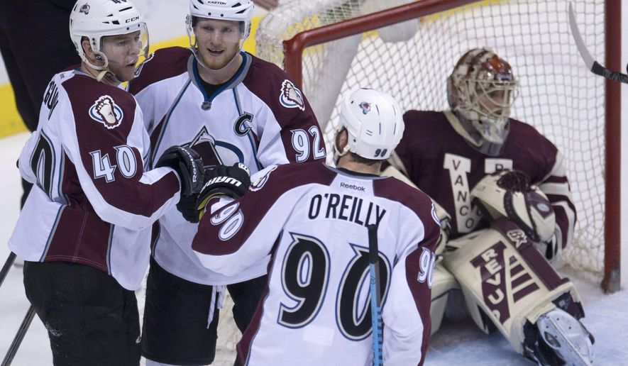 Colorado Avalanche left wing Alex Tanguay (40) celebrates his goal past Vancouver Canucks goalie Eddie Lack (31) with teammates Ryan O'Reilly (90) and Gabriel Landeskog (92) during the second period of an NHL hockey game Thursday, March 26, 2015, in Vancouver, British Columbia. (AP Photo/The Canadian Press, Jonathan Hayward)
