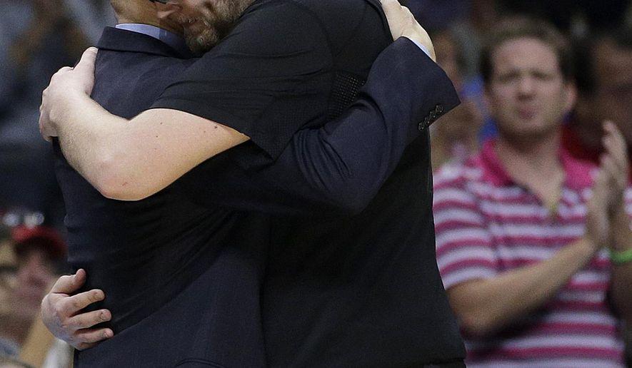 Xavier center Matt Stainbrook hugs Xavier head coach Chris Mack after losing to Arizona 68-60 in a college basketball regional semifinal in the NCAA Tournament, Thursday, March 26, 2015, in Los Angeles. (AP Photo/Jae C. Hong)