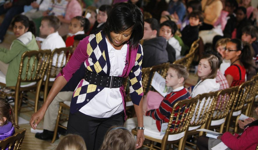 "In this April 23, 2009, file photo, first lady Michelle Obama speaks to children of executive office employees in the East Room of the White House in Washington, during the White House's annual ""Take Your Child to Work Day."" (AP Photo/Ron Edmonds, File)"