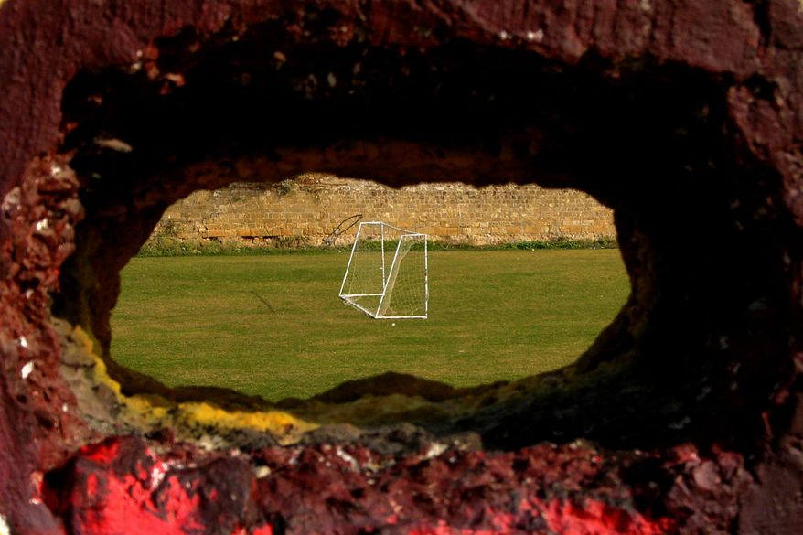 FILE - In this Wednesday, Nov. 6, 2013, file photo, a hole in a wall with a view of  a soccer pitch inside the United Nations controlled buffer zone separating ethnically-split Cyprus in the capital Nicosia. Six decades of soccer separation on ethnically divided Cyprus may be at its end as breakaway Turkish Cypriots are poised to join the ranks of the Cyprus Football Association to bring the sport under a single administrative roof. Cyprus Turkish Football Association International Relations Co-ordniator Deniz Birinci said on Friday, March 27, 2015, that Association President Hasan Sertoglu will on Monday set in motion the process to induct the CTFA into the Cyprus FA. (AP Photo/Petros Karadjias, File)