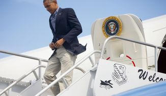 President Barack Obama walks down the stairs upon his arrival on Air Force One at St. Lucie International Airport, Saturday, March 28, 2015, in Fort Pierce, Fla. Obama kicked off the spring season on Saturday with a weekend getaway in Florida, golfing with buddies the upscale resort where he once caused a stir by hitting the links with Tiger Woods. (AP Photo/Pablo Martinez Monsivais)
