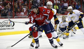 Washington Capitals right wing Tom Wilson (43) goes for the puck, with Nashville Predators defenseman Cody Franson (44) behind him, during the first period of an NHL hockey game Saturday, March 28, 2015, in Washington. (AP Photo/Alex Brandon)