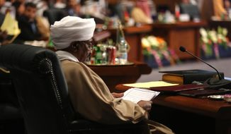 Sudanese President Omar al-Bashir reads a document during a meeting of Arab heads of state, in Sharm el Sheik, South Sinai, Egypt, Saturday, March 28, 2015. (AP Photo/Thomas Hartwell)