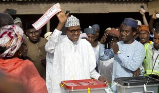 Opposition candidate Gen. Muhammadu Buhari holds his ballot paper in the air before casting his vote in his home town of Daura, northern Nigeria Saturday, March 28, 2015. Nigerians went to the polls Saturday in presidential elections which analysts say will be the most tightly contested in the history of Africa's richest nation and its largest democracy. (AP Photo/Ben Curtis)