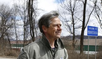 "Joe Sestak, a candidate seeking the Democratic Party nomination for the US Senate, passes a sign for the border between Pennsylvania and Ohio as he completes his ""Walking In Other Pennsylvanian's Shoes"", walking tour across the state of Pennsylvania on Saturday, March 28, 2015, in Ohioville, Pa. (AP Photo/Keith Srakocic)"