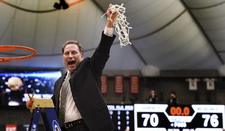 Michigan State coach Tom Izzo holds up the net after his team defeated Louisville 76-70 in overtime in the NCAA men's college basketball tournament East Regional in Syracuse, N.Y., Sunday, March 29, 2015. (AP Photo/Post-Standard, Kevin Rivoli)