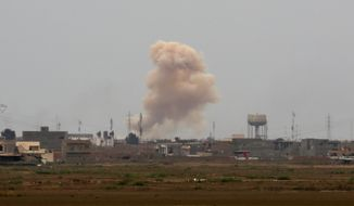 Smoke rises from central Tikrit as Iraqi security forces attack Islamic State extremist positions 130 kilometers (80 miles) north of Baghdad, Iraq, Sunday, March 29, 2015. (AP Photo/Khalid Mohammed)