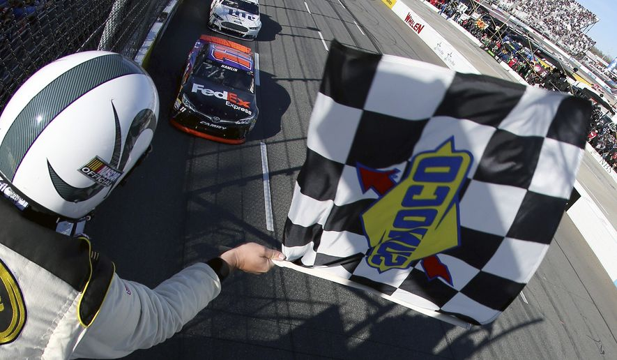 In a file photo provided by NASCAR, Denny Hamlin (11) he takes the checkered flag to win the NASCAR Sprint Cup Series auto race at Martinsville Speedway on Sunday, March 29, 2015, in Martinsville, Va.  (AP Photo/NASCAR, Nick Laham) ** FILE **