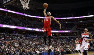 Houston Rockets guard Corey Brewer (33) dunks the ball in front of Washington Wizards guard Bradley Beal (3) in the first half of an NBA basketball game Sunday, March 29, 2015, in Washington. (AP Photo/Alex Brandon)