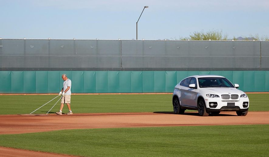In this March 26, 2015 photo provided by the Cleveland Indians, workers maintain the field as rookie infielder Jose Ramirez's car is parked on the infield dirt, at the Cleveland Indians practice facility in Goodyear, Ariz. After noticing the car sitting too far from the curb, infielder Mike Aviles orchestrated the prank, which involved getting Ramirez's keys and driving it onto a practice field. (AP Photo/Cleveland Indians, Dan Mendlik)