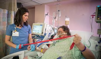 In this photo provided by the Wake Forest Baptist Medical Center, taken March 11, 2015, in the intensive care unit at Wake Forest Baptist Medical Center, physical therapist Katie Kellner helps patient Terry Culler do some exercises and briefly stand despite being hooked to a ventilator. There's increasing evidence that mild exercise may have its place even for the sickest ICU patients. (AP Photo/Warren Cameron Dennis III, Wake Forest Baptist Medical Center)