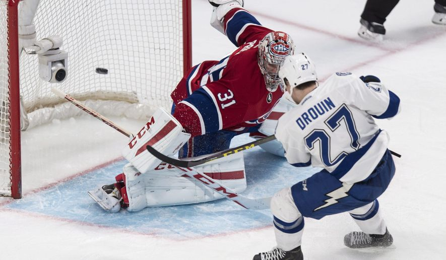 Tampa Bay Lightning's Jonathan Drouin scores past Montreal Canadiens goalie Carey Price during the second period of an NHL hockey game Monday, March 30, 2015, in Montreal. (AP Photo/The Canadian Press, Paul Chiasson)