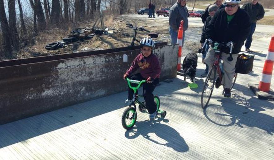 In a Saturday, March 28, 2015 photo, Maddox Schwalm-Bell, 4, is the first person to ride across the newly completed trail bridge next to the Mehaffey Bridge over the Iowa River and Coralville Lake in rural Johnson County, Iowa. The bridge was open to foot and bike traffic temporarily. On Monday, the trail bridge will be used for single-lane vehicle traffic while the rest of the bridge is worked on. (AP Photo/Iowa City Press-Citizen,  Jeff Charis-Carlson) NO SALES