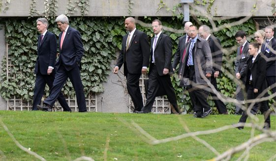 Secretary of State John F. Kerry (second from left) and British Foreign Secretary Philip Hammond (left) take a walk during a break in talks on Iran's nuclear program in Lausanne, Switzerland. The U.S. and five allies have been meeting with Iranian negotiators for days in a last-ditch try to hammer out the blueprint for a final deal by the end of June. (Associated Press)