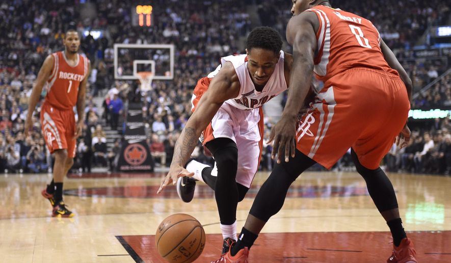 Toronto Raptors' DeMar DeRozan and Houston Rockets' Joey Dorsey battle for the ball during first half of an NBA basketball game in Toronto, Monday, March 30, 2015. (AP Photo/The Canadian Press, Frank Gunn)