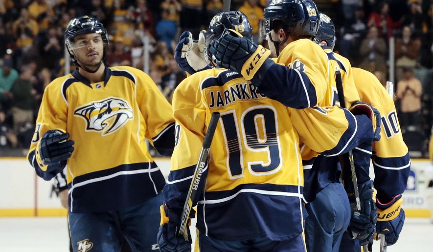Nashville Predators defenseman Seth Jones, left, joins the celebration after a goal by defenseman Roman Josi (59), of Switzerland, against the Calgary Flames in the first period of an NHL hockey game Sunday, March 29, 2015, in Nashville, Tenn. (AP Photo/Mark Humphrey)