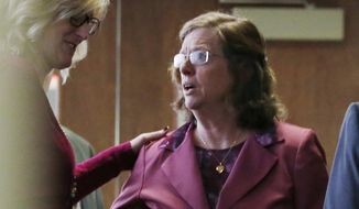 """File--In this file photograph taken on Monday, Dec. 8, 2014, an unidentified woman, left, consoles Arlene Holmes, right, as she leaves the courtroom after a pretrial readiness hearing in Centennial, Colo., in the murder trial of her son, James Holmes, who is charged with killing 12 moviegoers and wounding 70 more in a shooting spree in a crowded theater in Aurora, Colo., in July 2012. Arlene Holmes and her husband, Bob, told the Del Mar Times in the couple's first interview since the mass shooting about the book she wrote after her son's rampage in which she said that she prays for the victims of the theatre rampage daily """"by name and by wound.""""  (AP Photo/David Zalubowski, File)"""