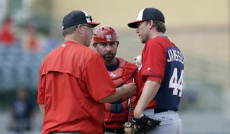 Washington Nationals pitching coach Steve McCatty talks with pitcher Casey Janssen during the sixth inning of a spring training exhibition baseball game against the Houston Astros in Kissimmee, Fla., Sunday, March 15, 2015. (AP Photo/Carlos Osorio)
