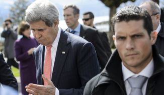 "U.S. Secretary of State John Kerry, left, gestures as he takes a break from the latest round of talks on Iran's nuclear program Monday in Lausanne, Switzerland. ""We are working late into the night and obviously into tomorrow,"" Mr. Kerry said. ""Everyone knows the meaning of tomorrow."" (Associated Press)"